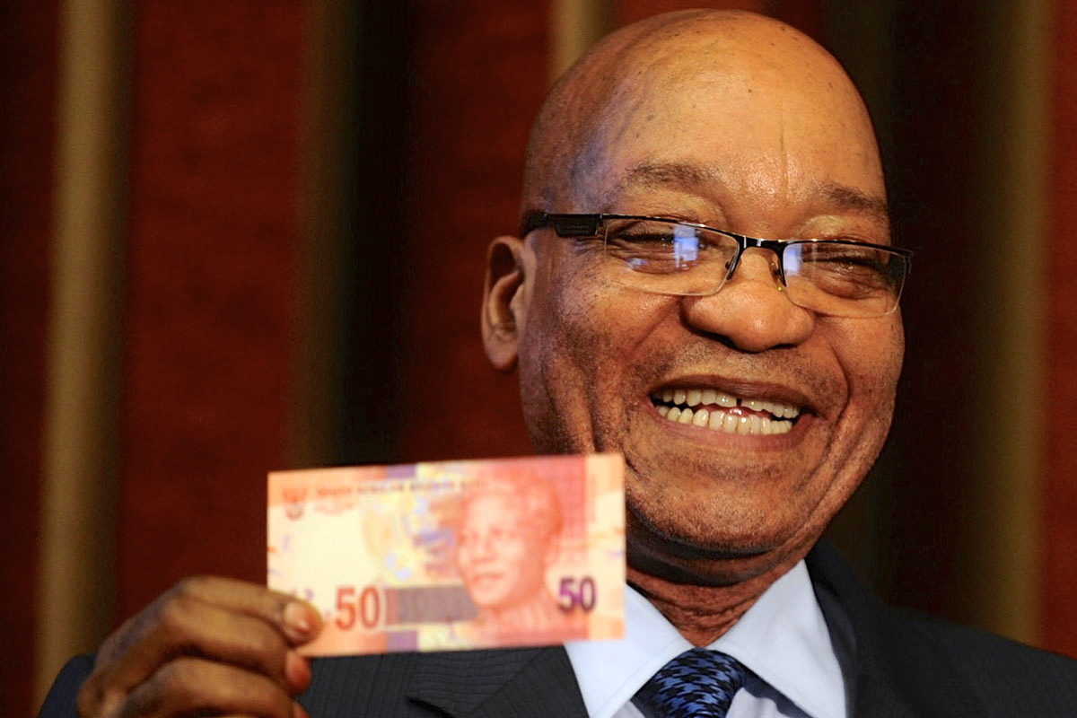 South Africa's President Jacob Zuma holds up a banknote bearing the face of former president Nelson Mandela in Pretoria February 11, 2012. Zuma on Saturday announced the launch of new notes bearing the image of Mandela to coincide with the 22nd anniversary of Mandela's release from prison. REUTERS/Stringer (SOUTH AFRICA - Tags: POLITICS BUSINESS TPX IMAGES OF THE DAY) - RTR2XNTG